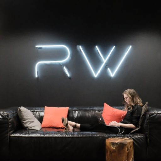 Designer working on laptop on couch under neon Rocket Wagon sign